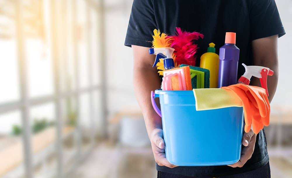 a man holding cleaning supplies
